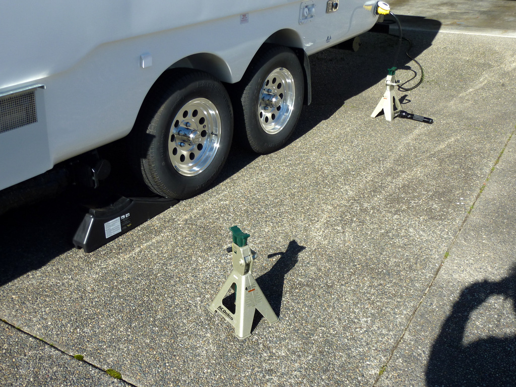Trailer on driveway with brake adjustment equipment