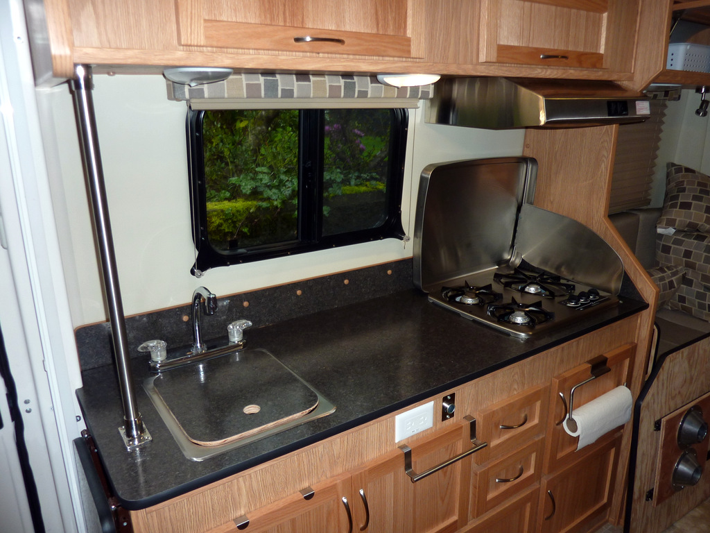 Toto's kitchen, starboard side. A sink, a counter, a propane cooktop and some cabinets.