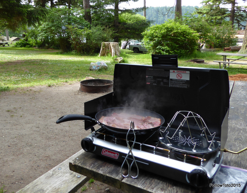 Bacon cooking on camp stove.