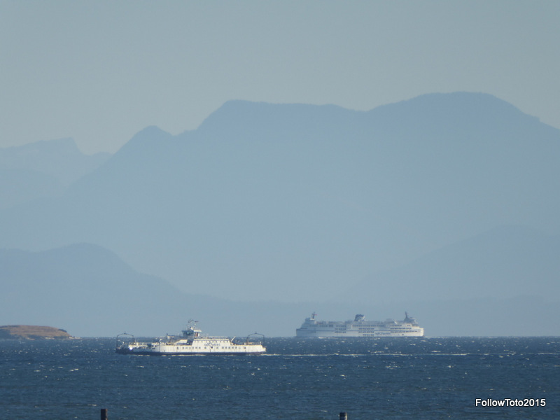Big ferry, little ferry, mountains behind.