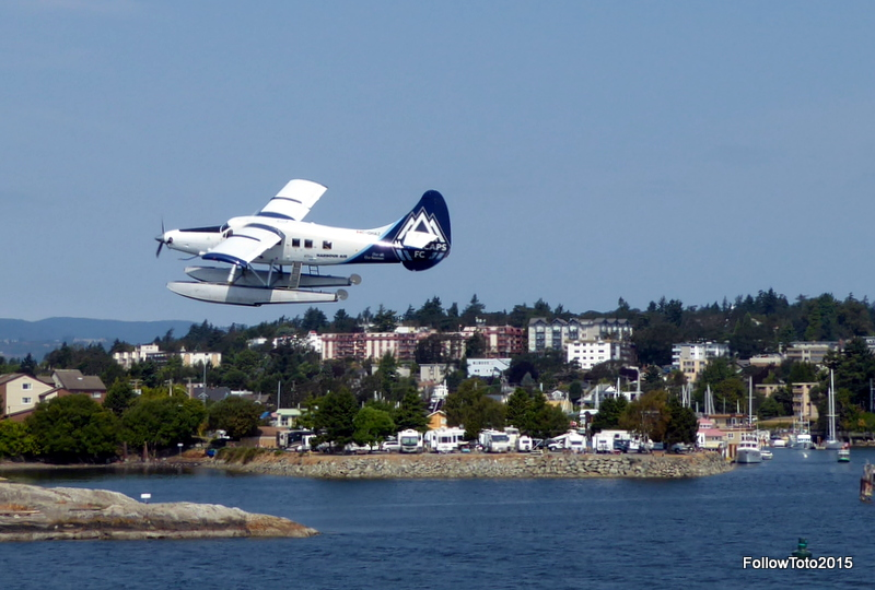 Float plane taking off, RV park, western part of Victoria Harbour, Esquimalt high-rises on a hill in the background.