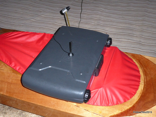 Cellphone booster antenna stuck to closed top of camp stove, which sits atop a kayak on the ground.