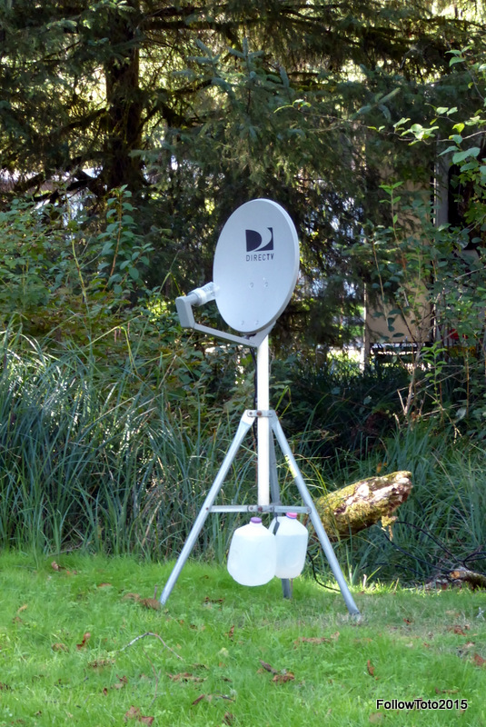 DirecTV dish on a tripod. A coax cable snakes its way through the trees toward a large RV.