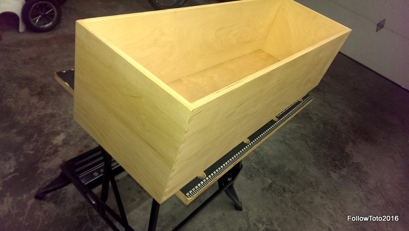 A long, tall drawer box sitting on a portable workbench in a tidy garage.